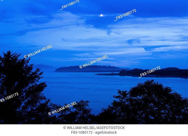 USA, Oregon, Tillamook County, Tillamook Bay looking west at dusk with setting moon, August