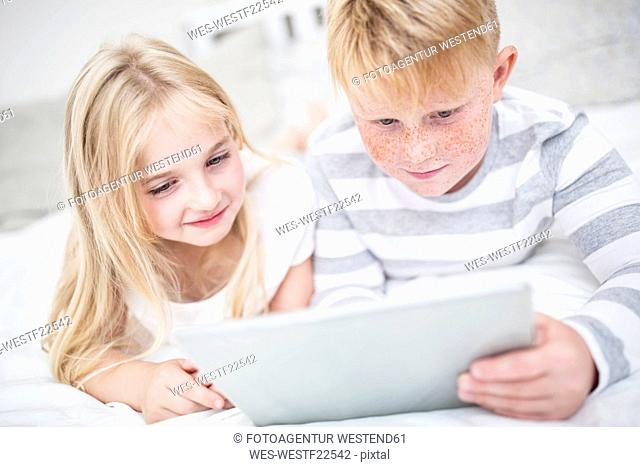 Brother and sister lying in bed using tablet