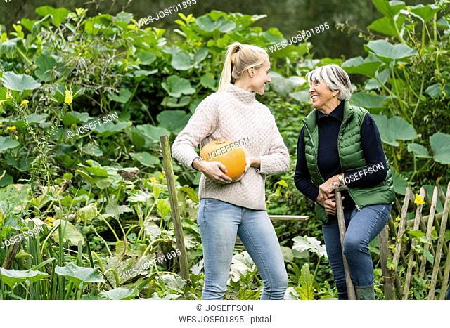 Happy young woman with her grandmother holding pumpkin in garden