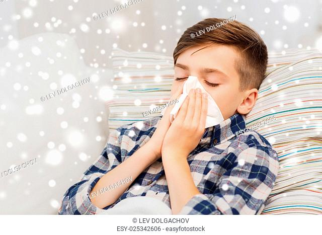 healthcare, rhinitis, people and medicine concept - ill boy with flu lying in bed and blowing his nose at home over snow