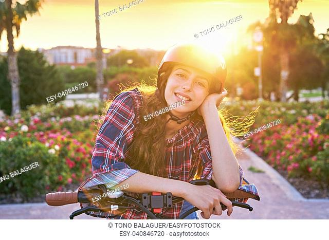 Girl portrait on bicycle with helmet smiling happy at the flowers park outdoor