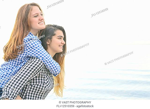 Side view of two teenage girls at the water's edge, one giving a ride to her friend on her back,Woodbine Beach; Toronto, Ontario, Canada