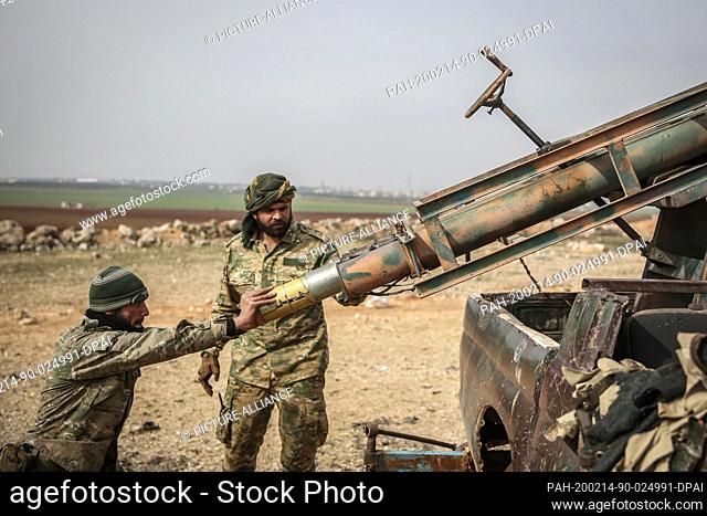 14 February 2020, Syria, Mizanaz: Turkish-backed Syrian fighters load missiles into a rocket launcher amid a massive attack to retake control of the town of...
