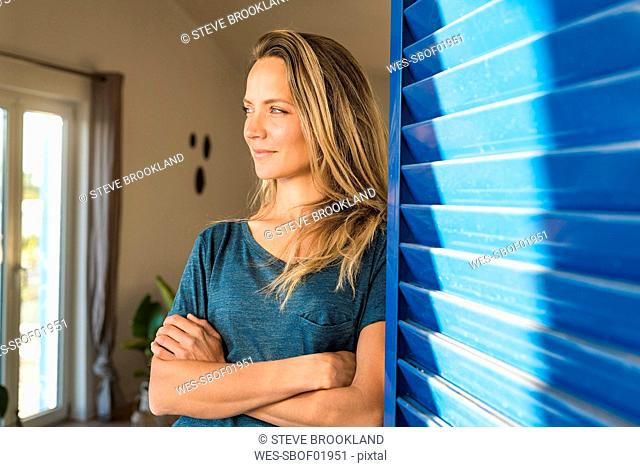 Woman leaning at open window at home looking sideways