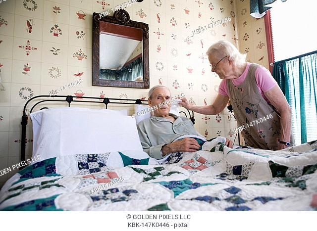 Senior woman affectionately tending to bedridden senior man