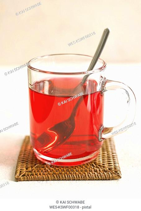 Glass of Hibiscus flower tea on table mat, close-up