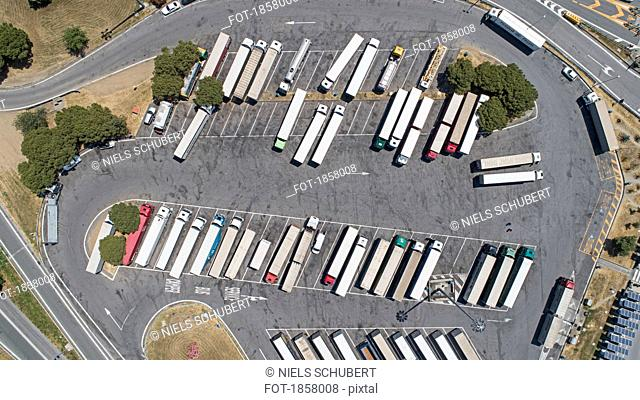 Aerial view from above semi-trucks parked in sunny rest stop parking lot