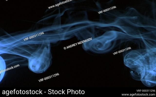 Vertical video screensaver - Trickle blue smoke slowly rising graceful twists up on black background. Cigar smoke blowing from the left side