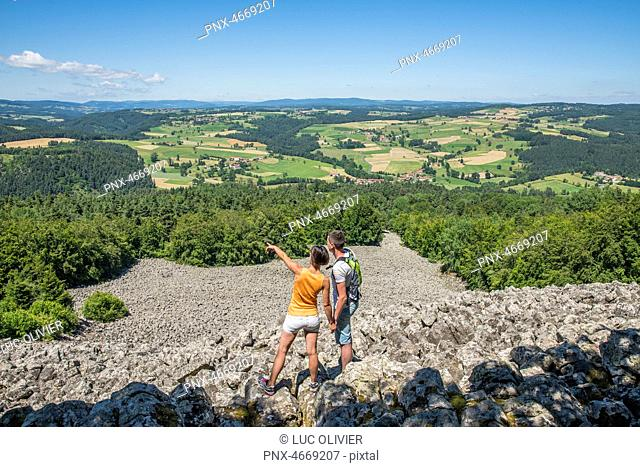 Auvergne - Rhone-Alpes - Haute-Loire - Saint-Julien-d'Ance - A couple on the Bourianne lava flow watching the view over the whole plain