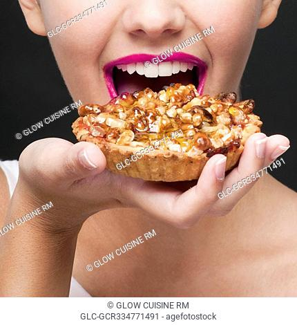 Close-up of a woman eating a tart