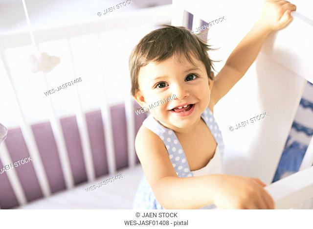 Portrait of happy baby boy in cot