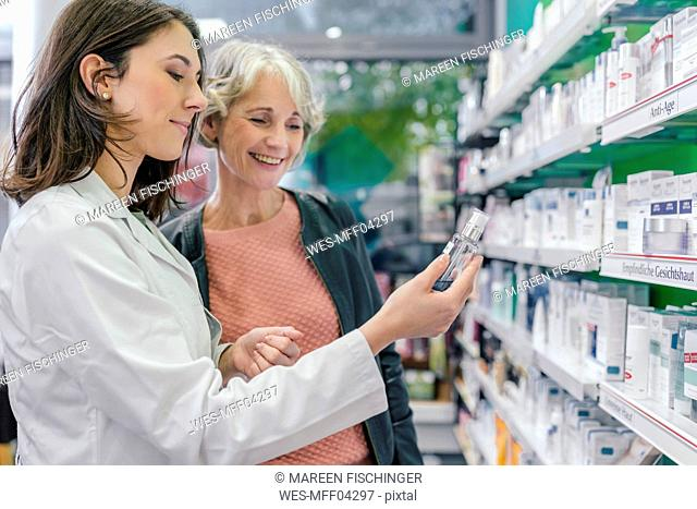 Pharmacist advising customer with cosmetics in pharmacy