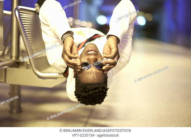 young man laying upside down on bench in underground train station, touching sunglasses, in Munich, Germany