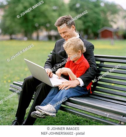 Businessman with small boy and laptop on park bench