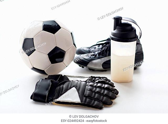 sport, soccer and sports equipment concept - close up of ball, football boots, goalkeeper gloves and protein shake bottle with drink