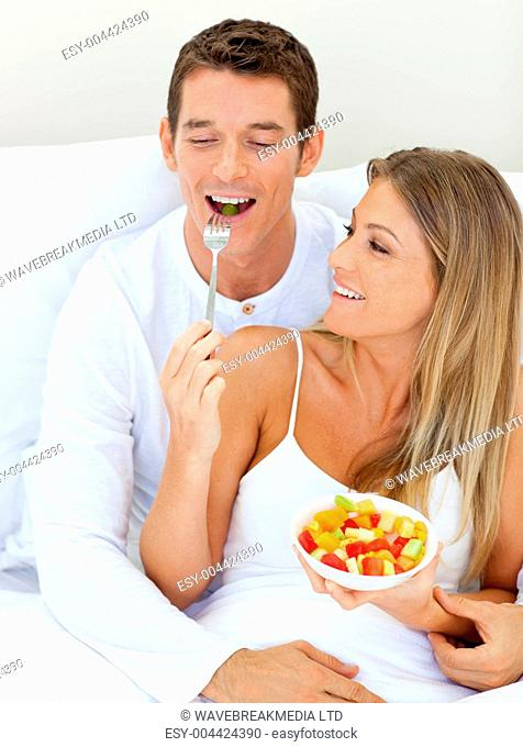 Jolly couple eating fruit lying on their bed
