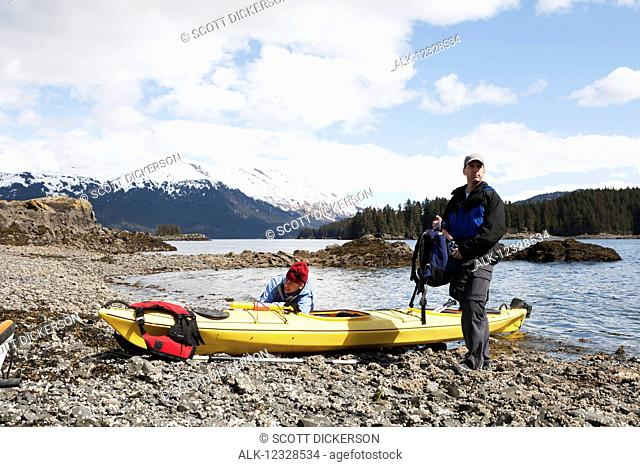 Two sea kayakers on shore with their boat, Kachemak Bay, South-central Alaska; Alaska, United States of America