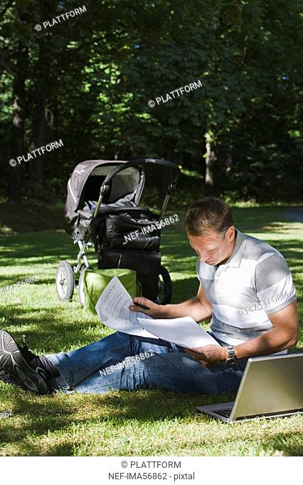 A man with a pram and a computer in a park a sunny day Sweden