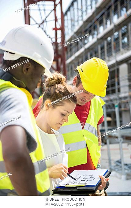 Architect reviewing blueprint with construction workers at building site
