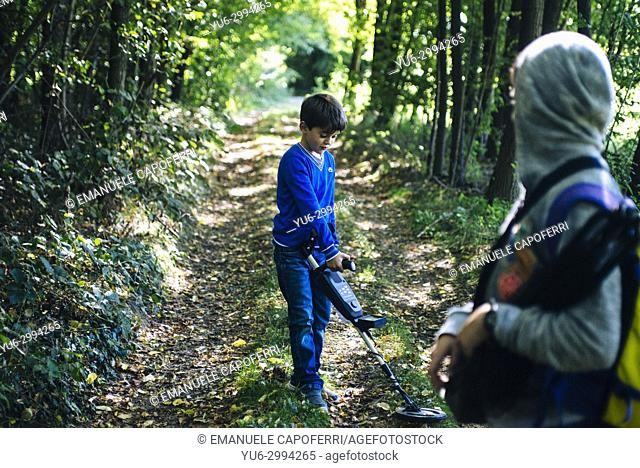 Children in the woods with metal detectors, Italy