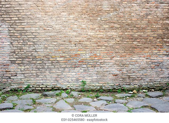 Antique stone wall behind a Roman pavement