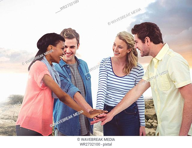 Happy Group of Friends cholding their hands against a Bright background