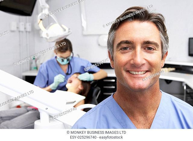 Portrait Of Dental Nurse With Dentist Examining Patient In Background