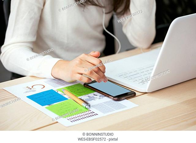 Close-up of woman with document, cell phone and laptop at desk in office