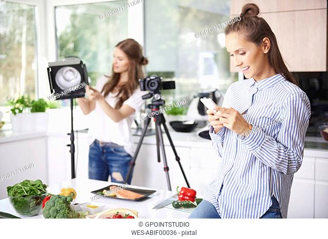Woman using smartphone before cooking