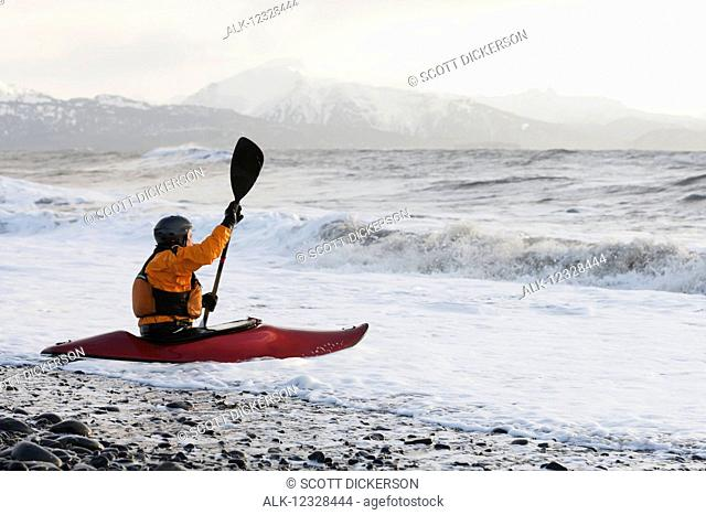Kayak surfer in a kayak enters Kachemak Bay, South-central Alaska; Homer, Alaska, United States of America