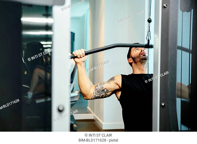 Man using exercise machine in gymnasium