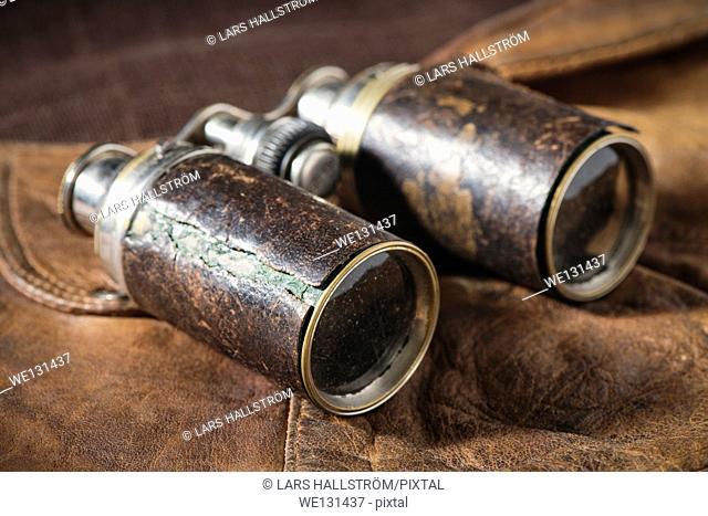 Close up of old fashioned binoculars lying on leather cap