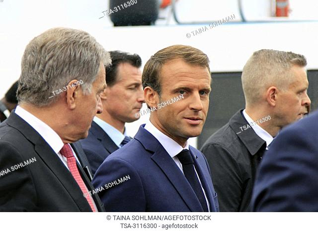 Helsinki, Finland. August 30, 2018. Finnish President Sauli Niinistö (L) and French President Emmanuel Macron (C) take a walk on the Market Square after their...