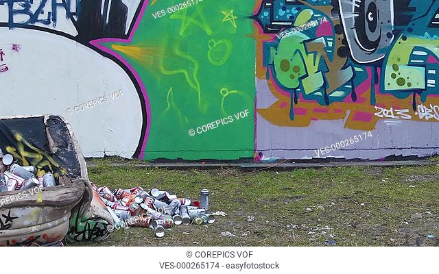 Pan over a graffiti wall, towards an artist at work, who is interrupted by law enforcement, and runs away, bailing out