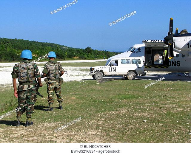 Soldiers of the 'United Nations Stabilisation Mission in Haiti' secure UN aircraft with machine gun and assault rifle next to unpaved runway, Haiti, Grande Anse