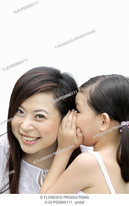 Young girl indoors whispering in woman's ear