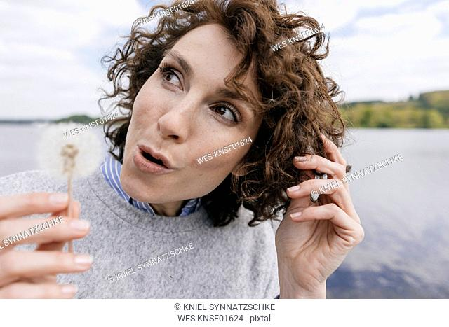 Woman at lake holding blowball