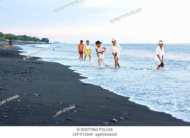 Children in shallow water at black sandy beach, Odalan, Pura Goa Lawah, Padangbai, Bali, Indonesia