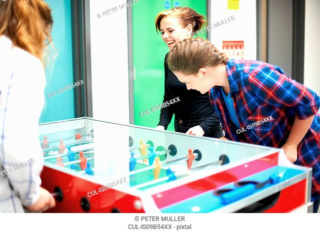 Group of female friends playing table football