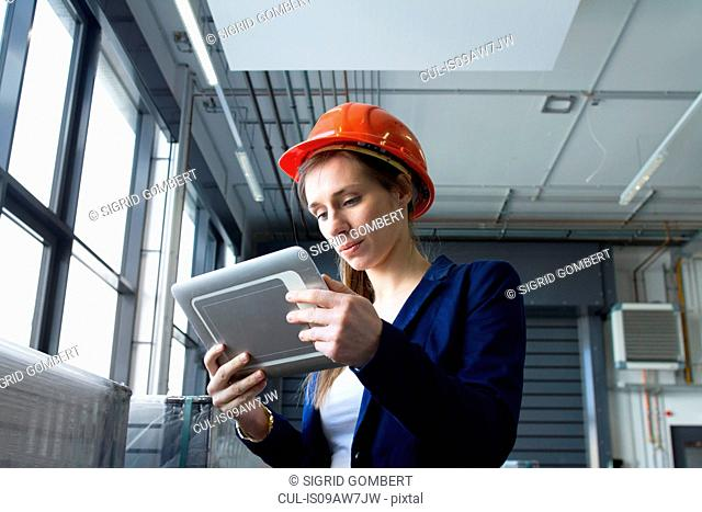 Woman in warehouse wearing hard hat looking at digital tablet