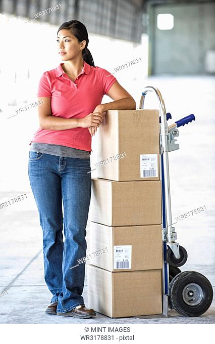 Black female standing next to hand truck in front of loading dock doors inside of a new warehouse