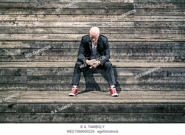 Businessman weraing suit and red sneakers sitting on wooden stairs