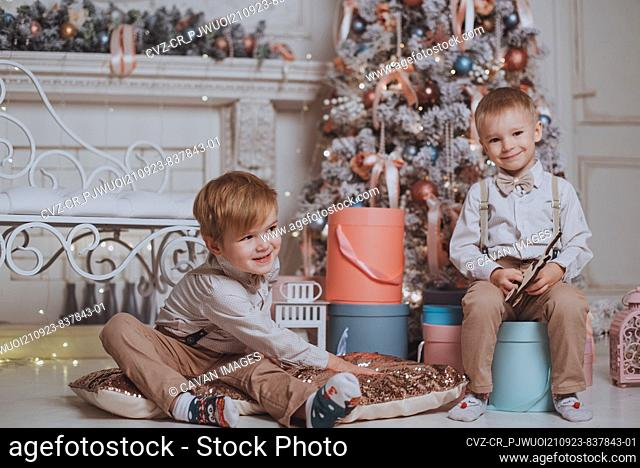 Cheerful cute children boys opening gifts under christmas tree