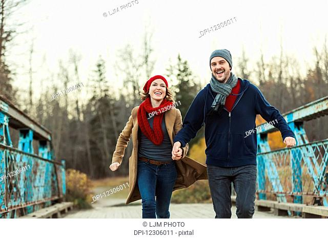 A young couple running on a bridge in a city park in autumn; Edmonton, Alberta, Canada