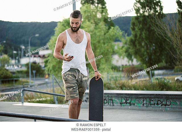 Young man in skatepark looking at cell phone