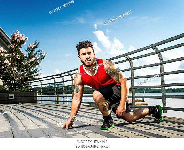 Young man training on lake pier