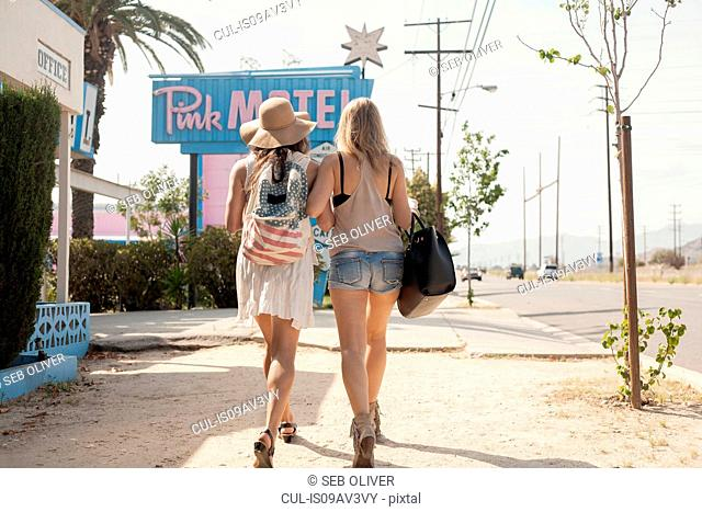 Female friends walking past motel, Los Angeles, California, USA