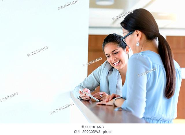 Businesswomen talking and using smartphone in office