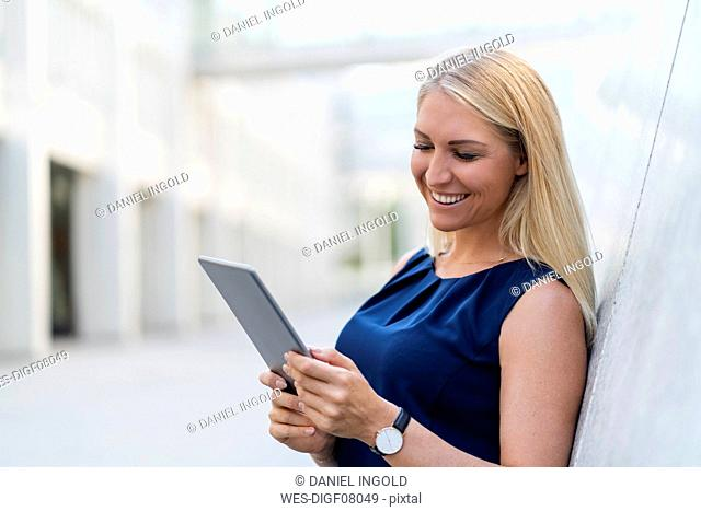 Portrait of smiling blond businesswoman looking at digital tablet