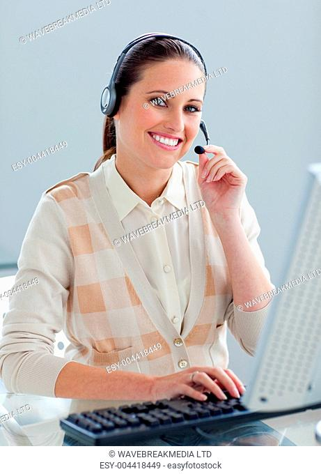 Self-assured businesswoman with headset on working at a computer